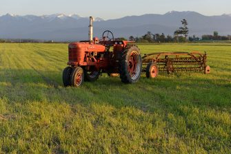 A red tractor in a farm field with mountains in the background