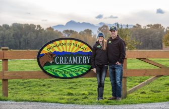 Sarah and Ryan McCarthy standing in front of the Creamery sign